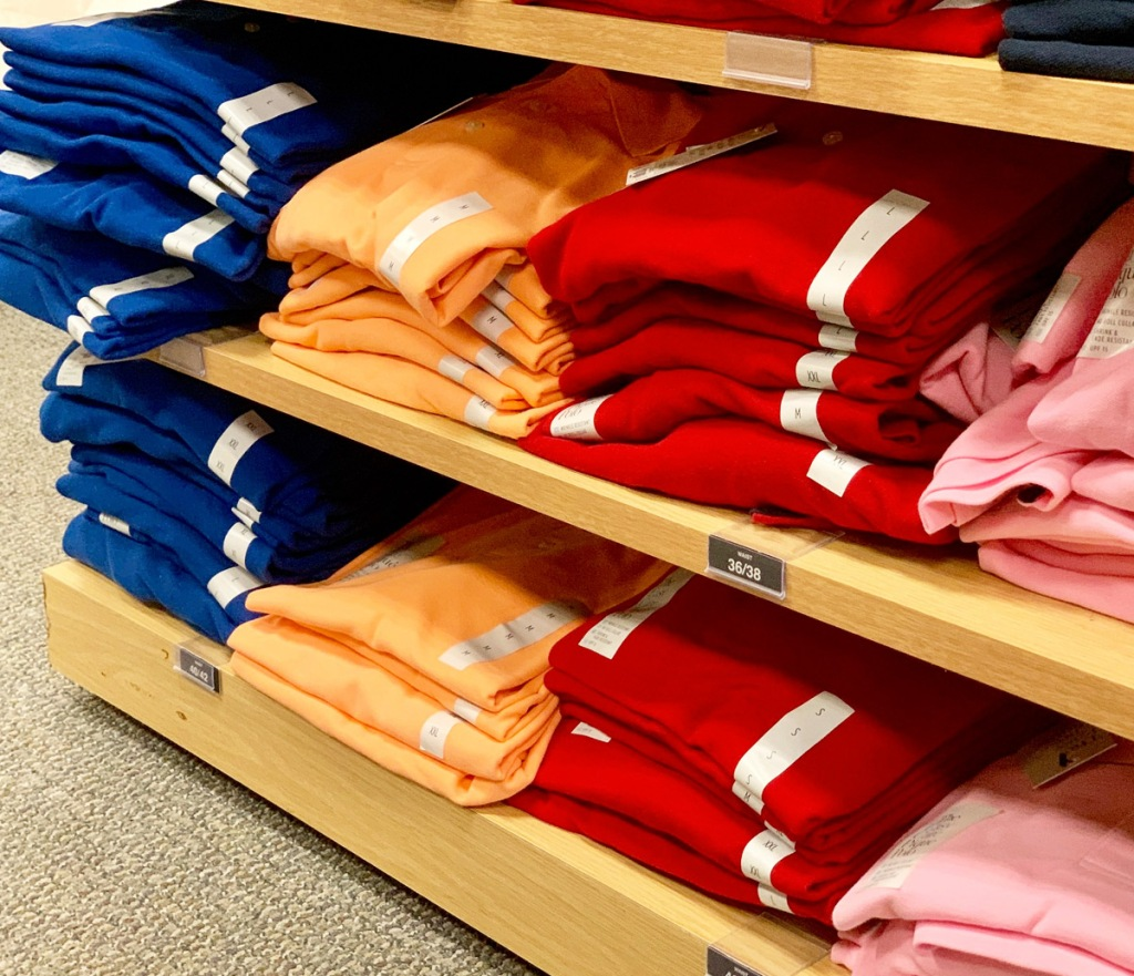 store display shelves with folded mens polo shirts in various colors
