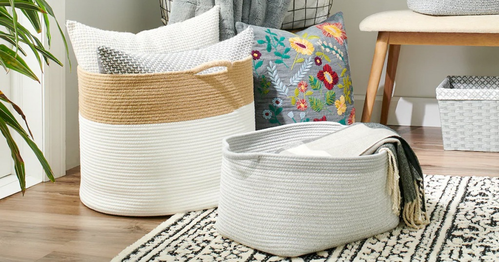 two woven rope laundry baskets on floor filled with throw pillows and blankets with more throw pillows in background