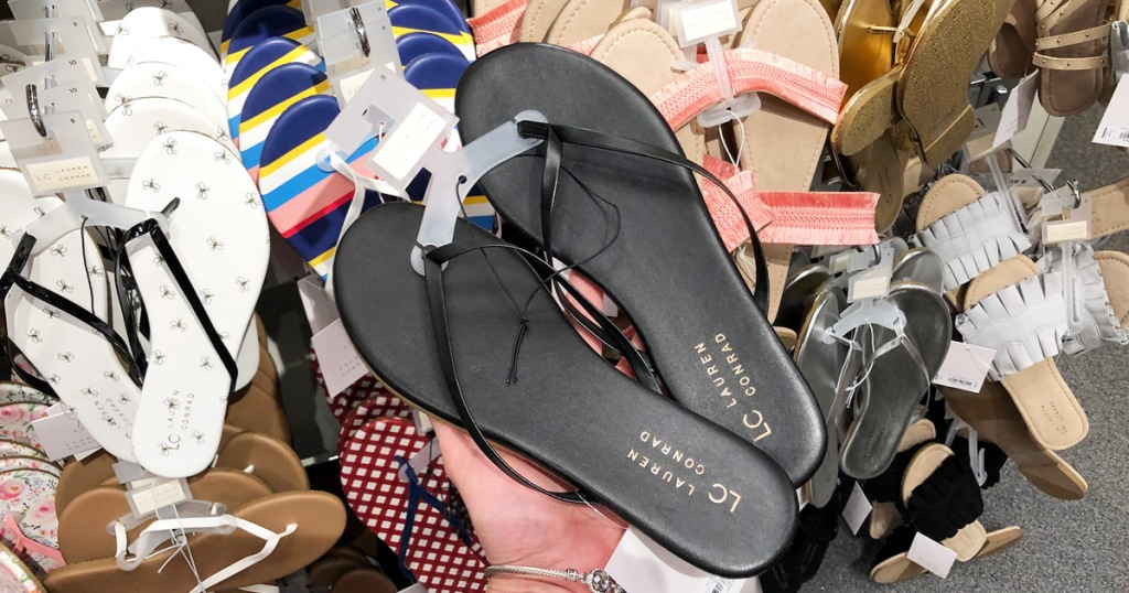 person holding up a black pair of womens flip flops in front of store display rack of sandals