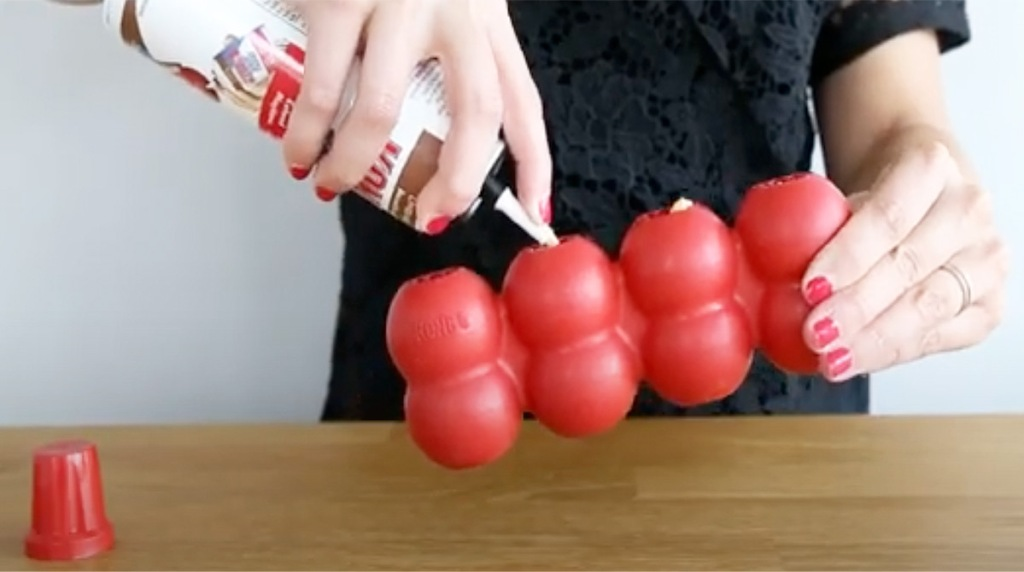 person spraying kong cheese into red toy