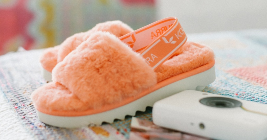 Koolaburra by UGG Fuzz'n peach slippers sitting on a bed next to a white camera