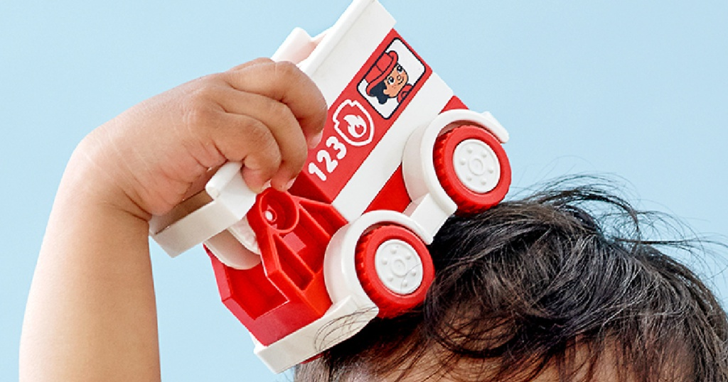 small child holding a lego duplo red fire truck on top of his head