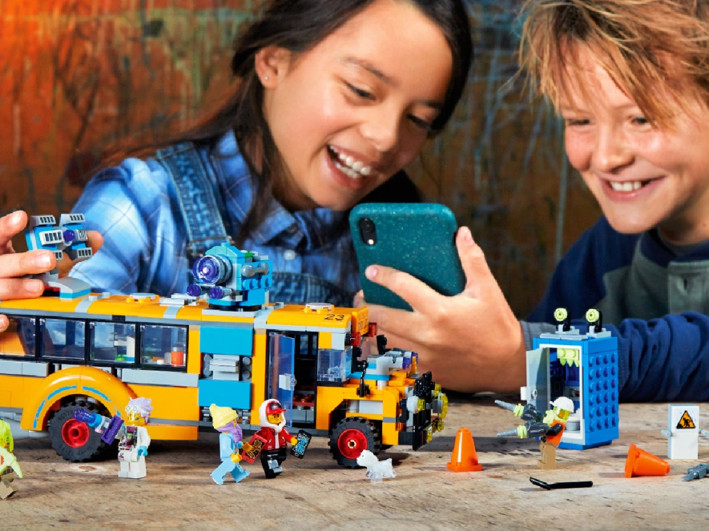 kids playing with a LEGO Hidden Side Paranormal Intercept Bus 3000 AR Building Kit