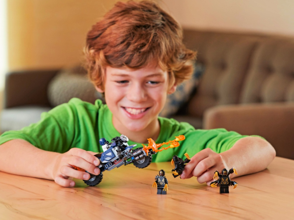 boy playing with a LEGO Marvel Avengers Captain America: Outriders Attack Building Set