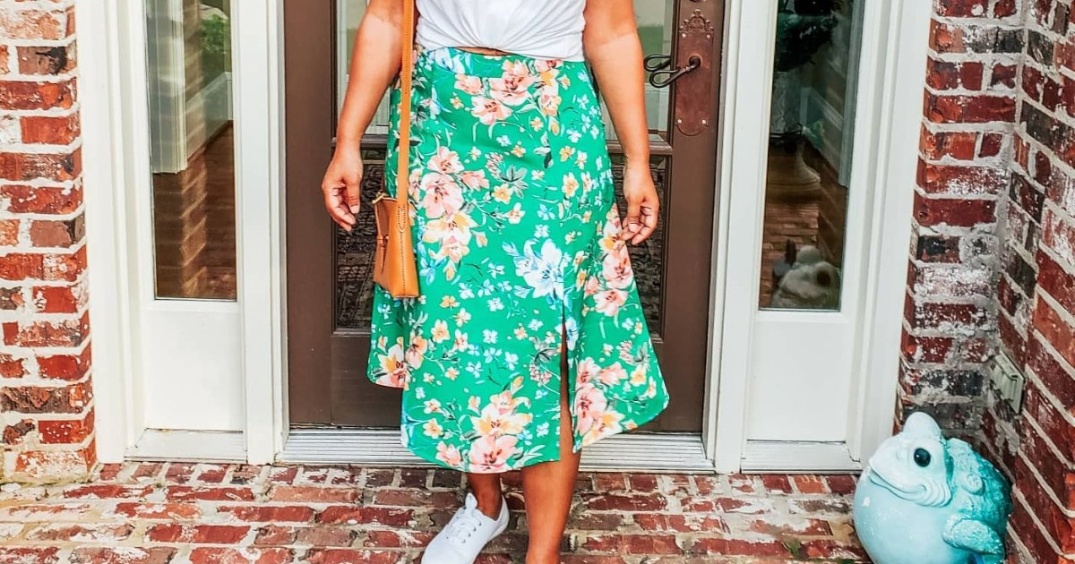 woman in white tee and green floral skirt standing in front of home
