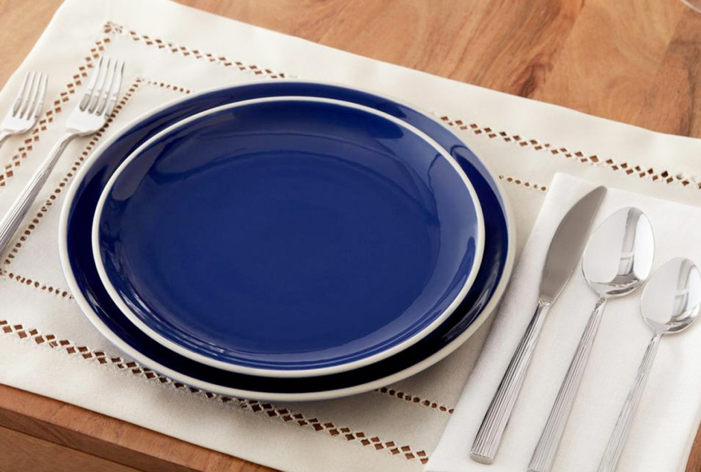 navy blue dinner and salad plate stacked on a white placemat with silverware on napkin