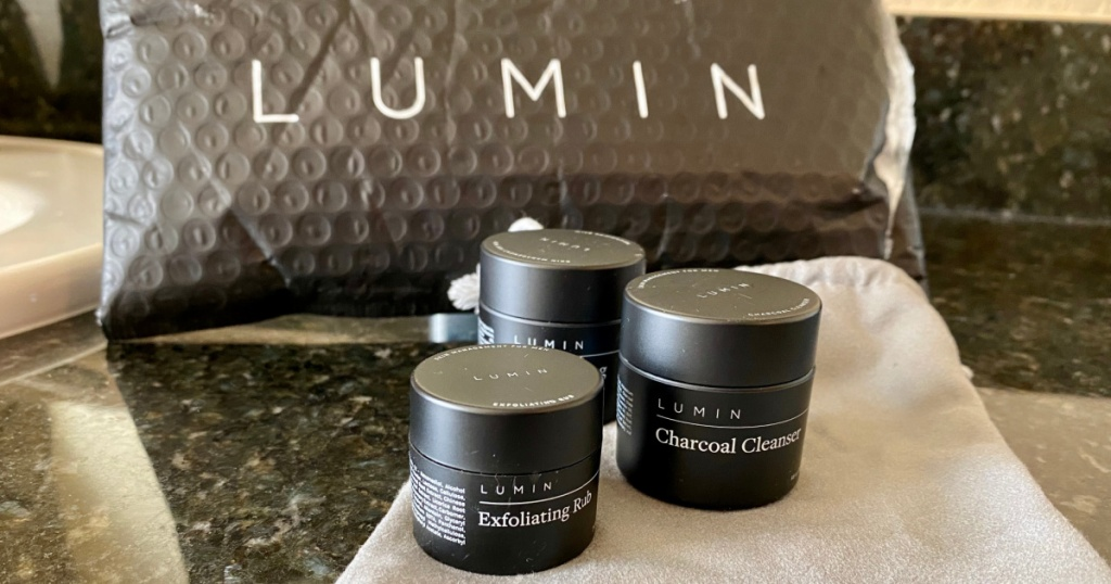 three small containers of lumin skincare products next to dust bag and shipping package