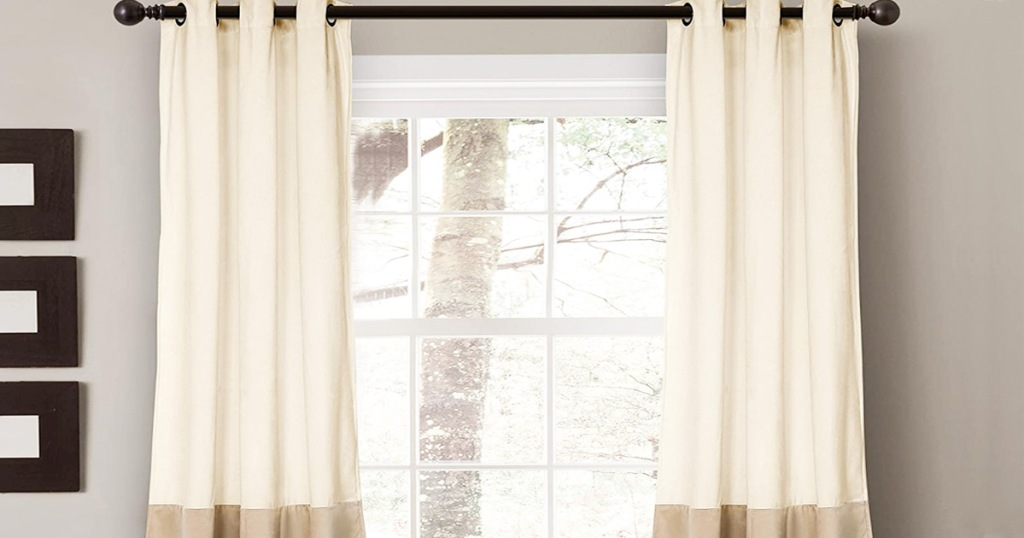 two velvet curtain panels on curtain rod in front of window in a ivory color with tan on the bottoms