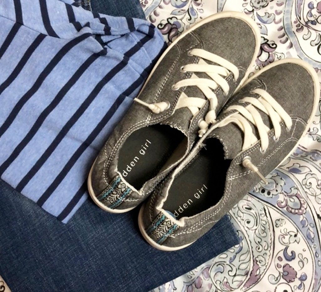 grey pair of slip on womens shoes on top of blue striped shirt and paisley print comforter