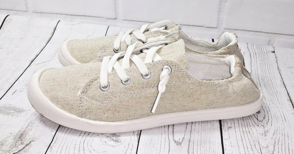 taupe colored slip on shoes on white wood