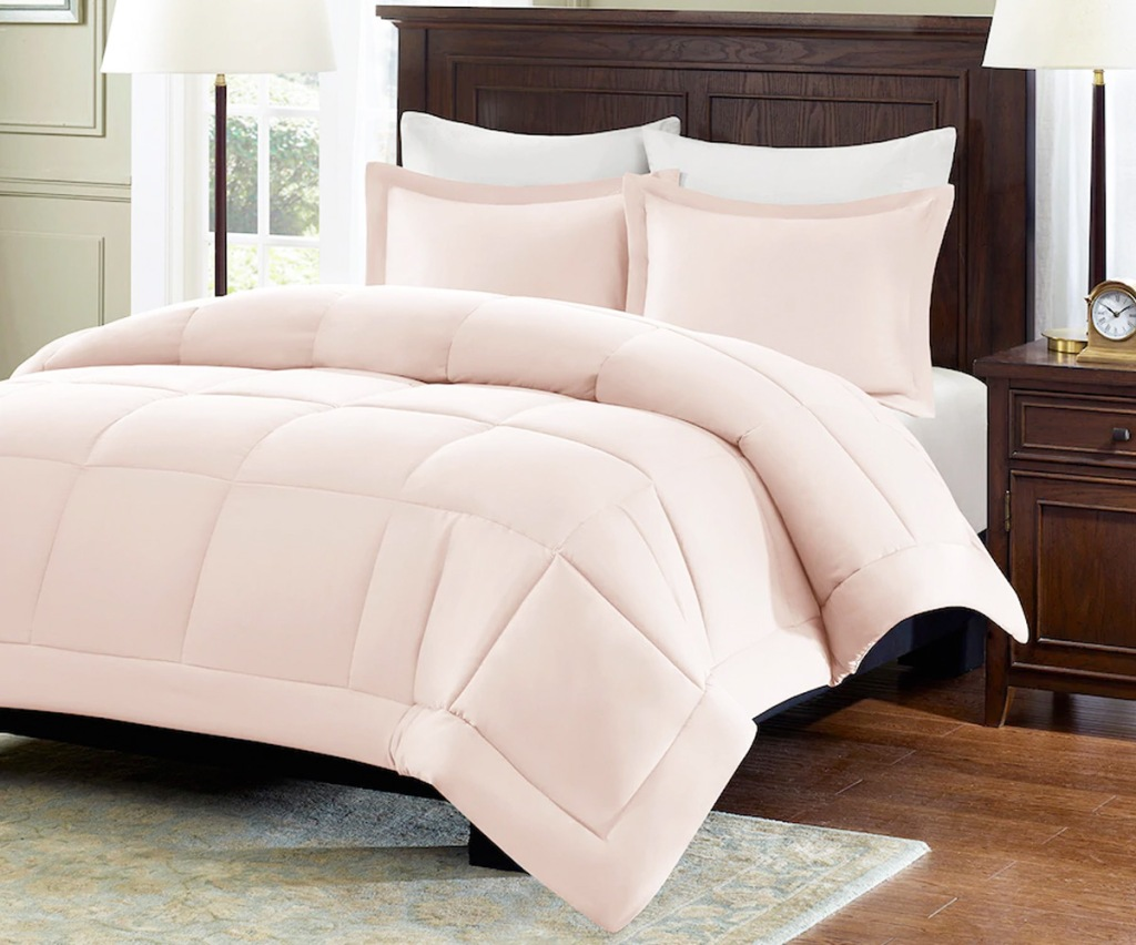 light pink comforter set on a bed with a dark brown headboard