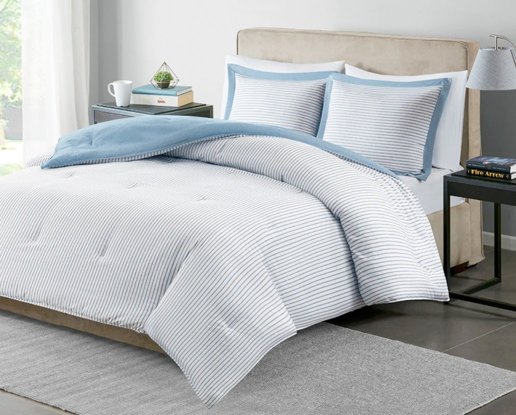 blue and white striped comforter set on bed with matching pillow shams