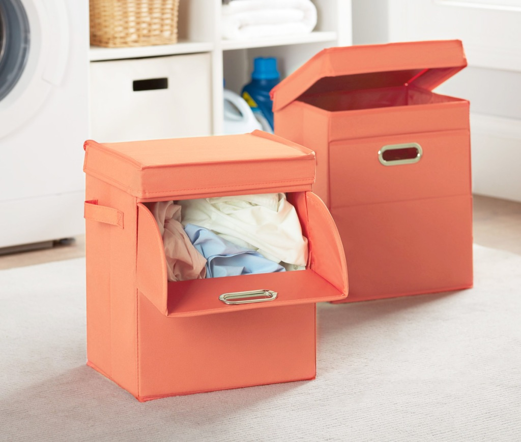 two orange cube shaped laundry hampers with front loading slot and lids