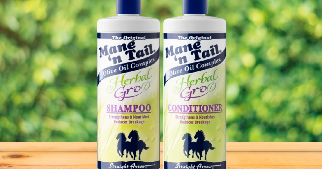 two bottles of shampoo on table with greenery in background