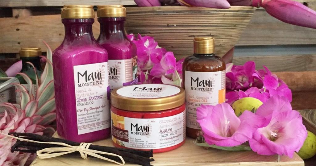 purple bottles of maui moisture hair care with purple flowers around them