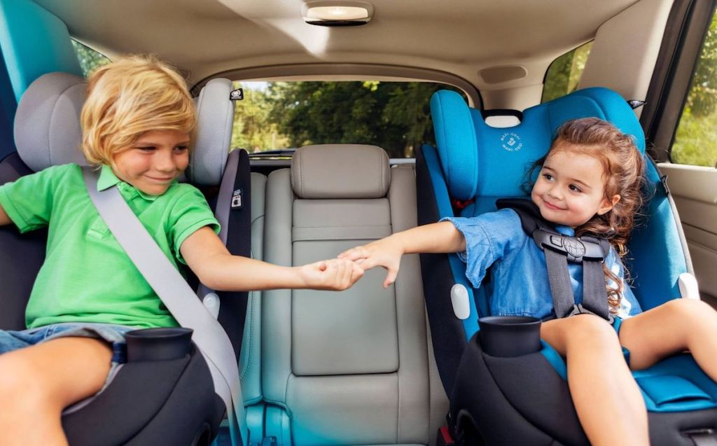 kids holding hands sitting in car seats