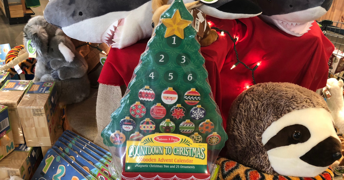 christmas tree advent calendar surrounded by stuffed animals and toys