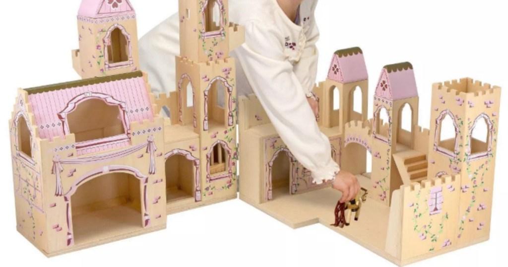 girl playing with Melissa & Doug folding princess castle