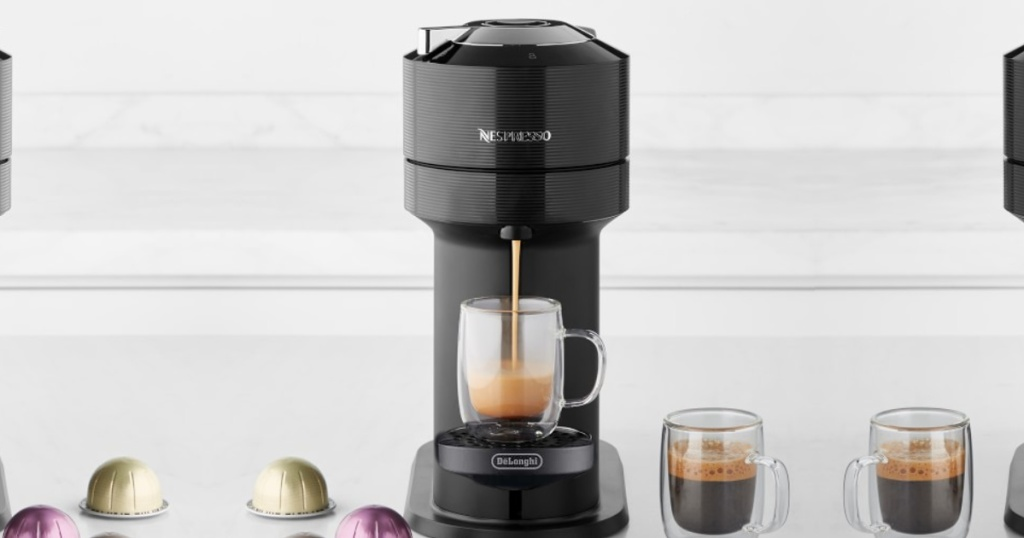 nespresso veruo next coffee maker on counter with cup of coffee being brewed and cup of coffee next to it