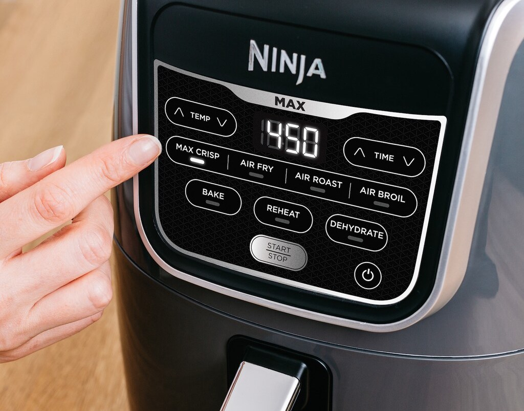 hand touching buttons on an air fryer