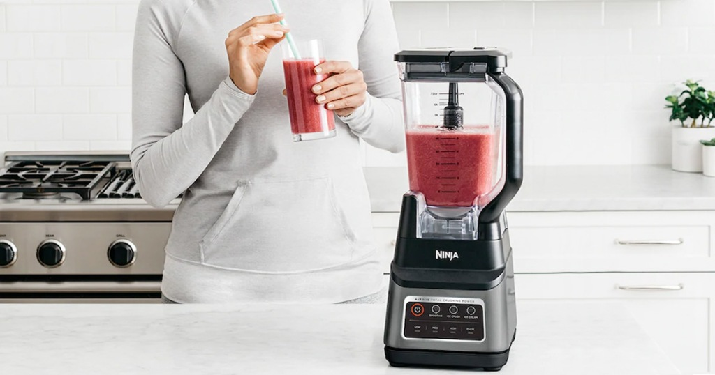 woman holding red smoothie standing next to kitchen counter with ninja blender