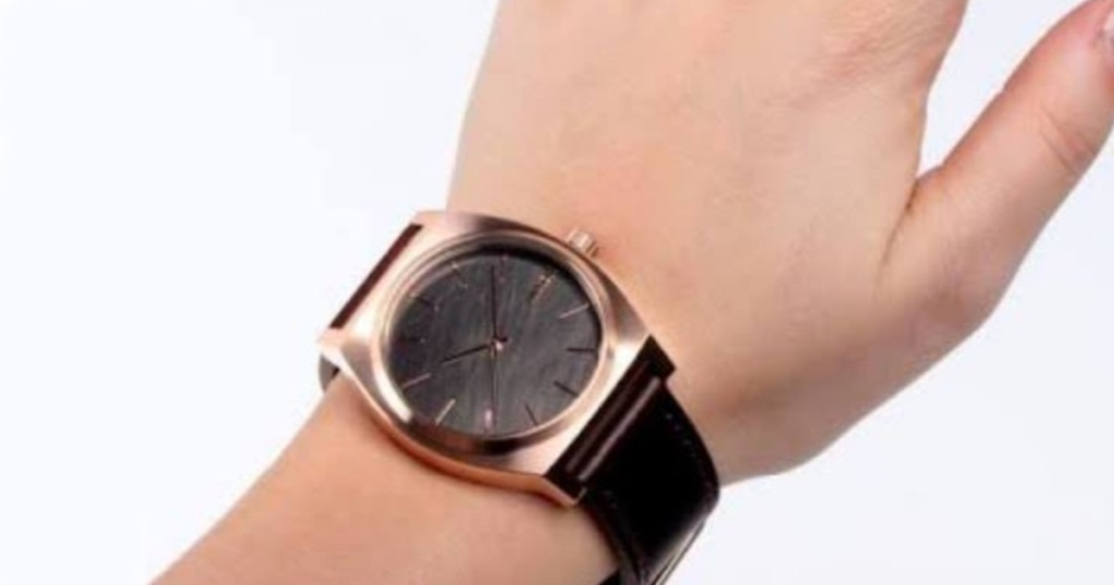 brown and gold watch on persons wrist.