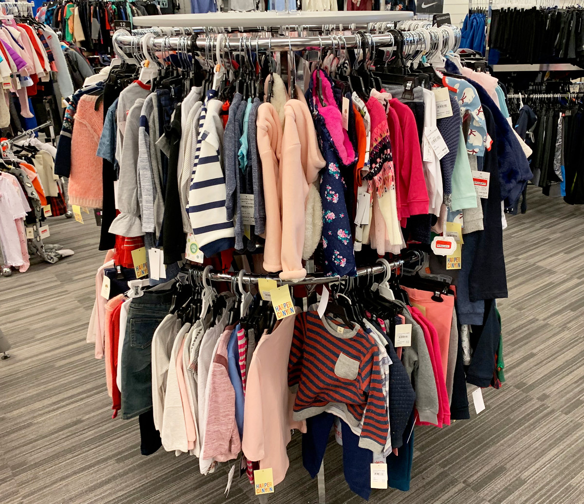 round store display rack with kids and baby apparel hanging on hangers