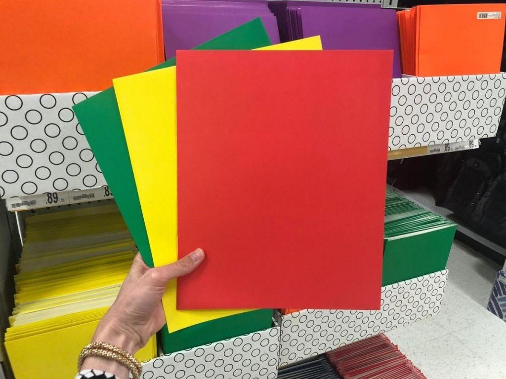 three folders in woman's hand