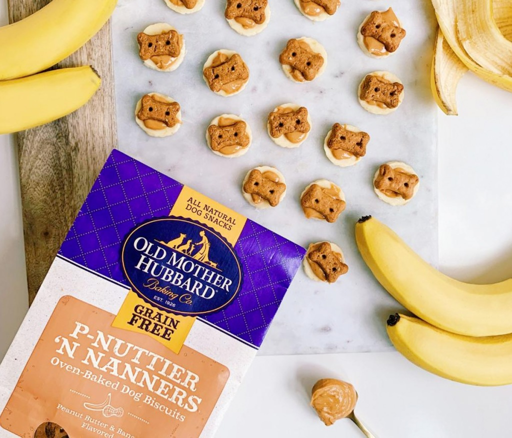 dog treat cookies with peanut butter and dog shaped bones on counter near bananas and bag of dog treats