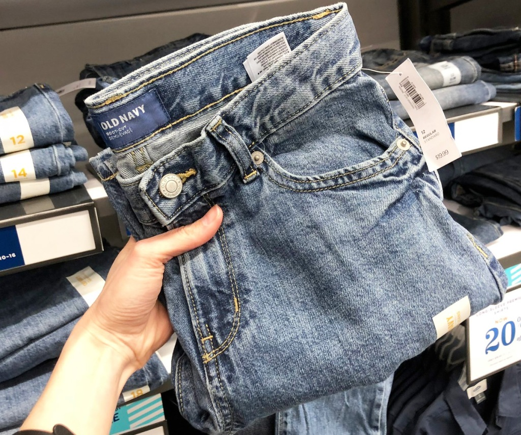 person holding up a pair of medium wash old navy boys jeans