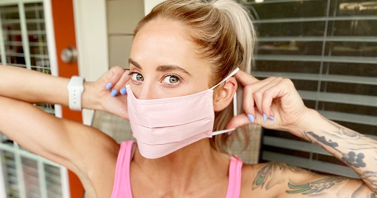 woman with blonde hair in pony tail putting on a light pink face mask