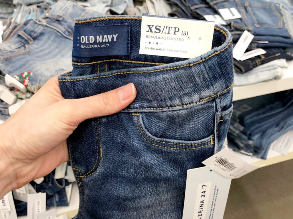 person holding up a pair of dark wash old navy girls jeans