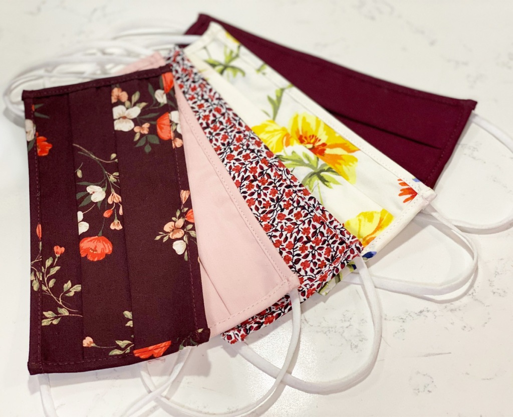 five reusable face masks laying on marble counter in various shades of pink and floral patterns