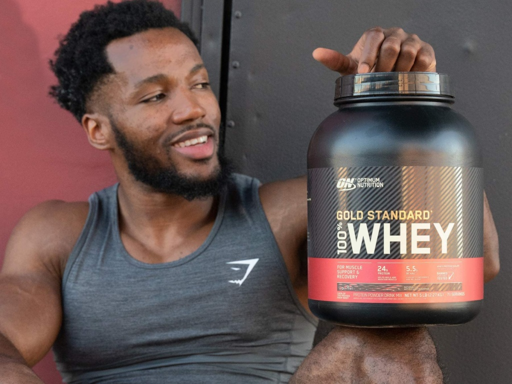 man sitting up against a wall wearing a tank top and holding a large container of Optimum Nutrition whey protein powder