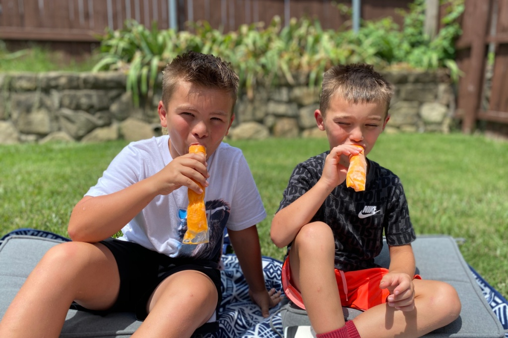 boys trying out orange popsicles