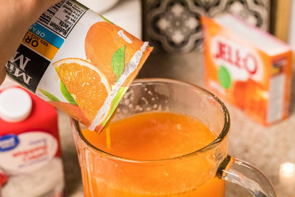pouring orange juice into pitcher