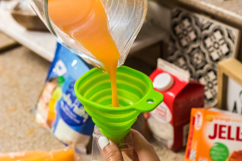 pouring popsicle mix into popsicle molds