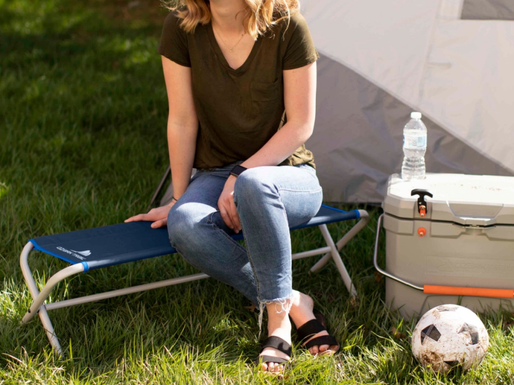 woman sitting on blue camping bench in grass, soccer ball, tent, and cooler