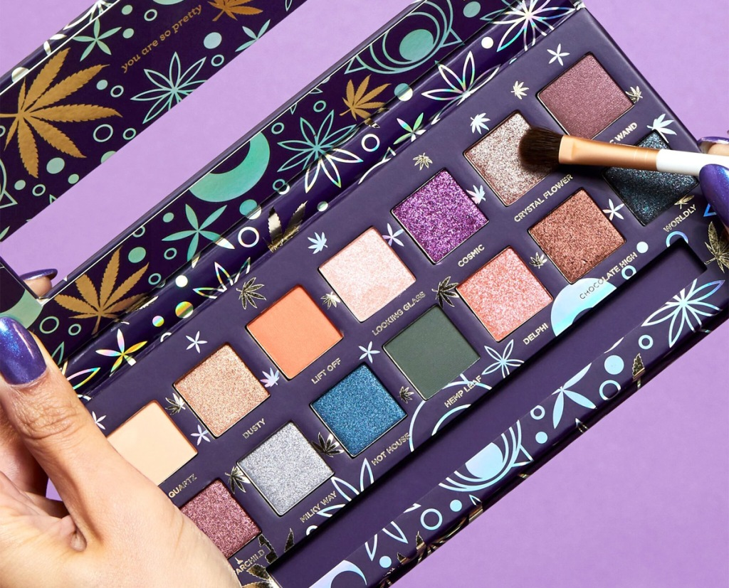 hand holding a purple themed eyeshadow palette with eyeshadow brush