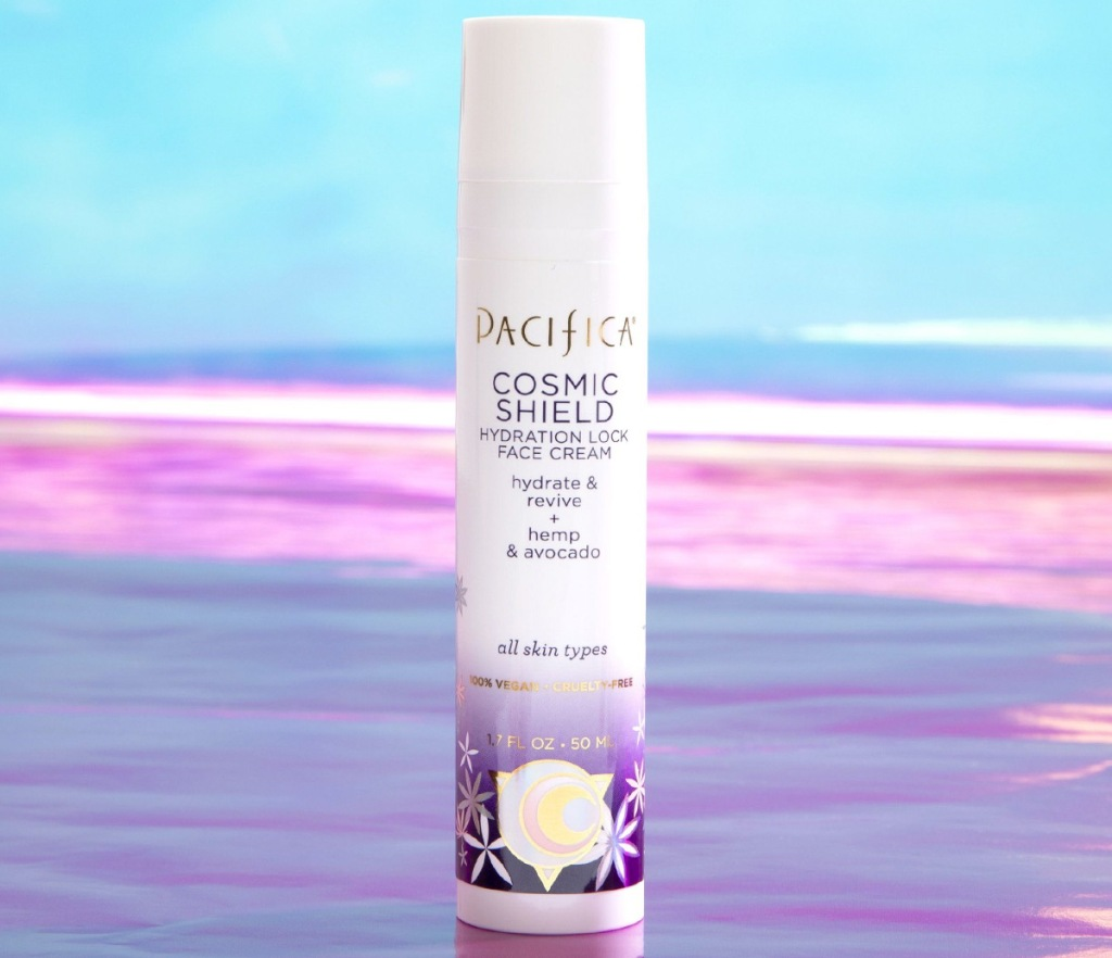 white and purple bottle of facial serum on a beach with pink and blue colors in background