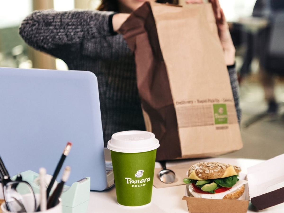 wanita di meja kerja dengan makanan, secangkir kopi, dan tas untuk dibawa