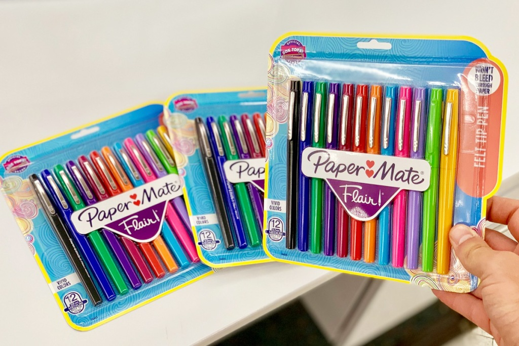 person holding package of multi colored papermate pens with two more packages in background