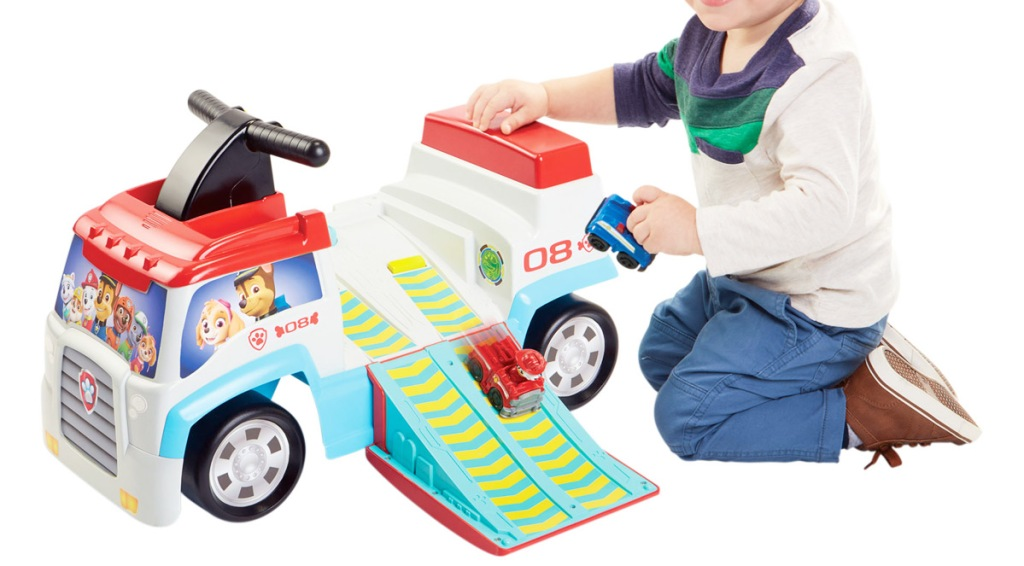 boy playing with cars on a ramp coming from a paw patrol themed ride-on toy