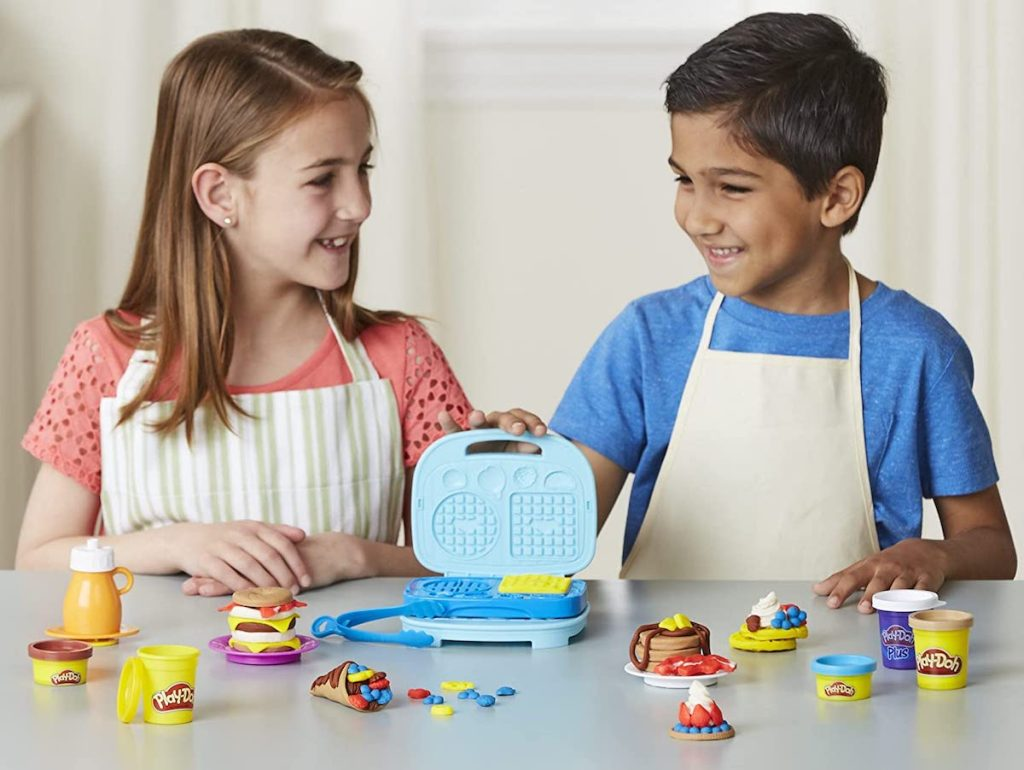 kids playing with a Play-Doh Bakery set