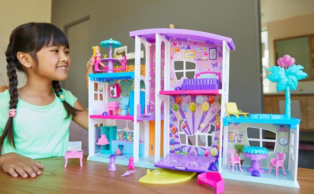 girl playing with doll playset