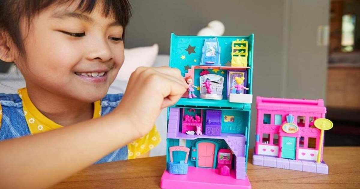 A young girl is playing with a Polly Pocket Play set on a table.