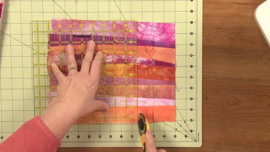 hands holding fabric down to cut it