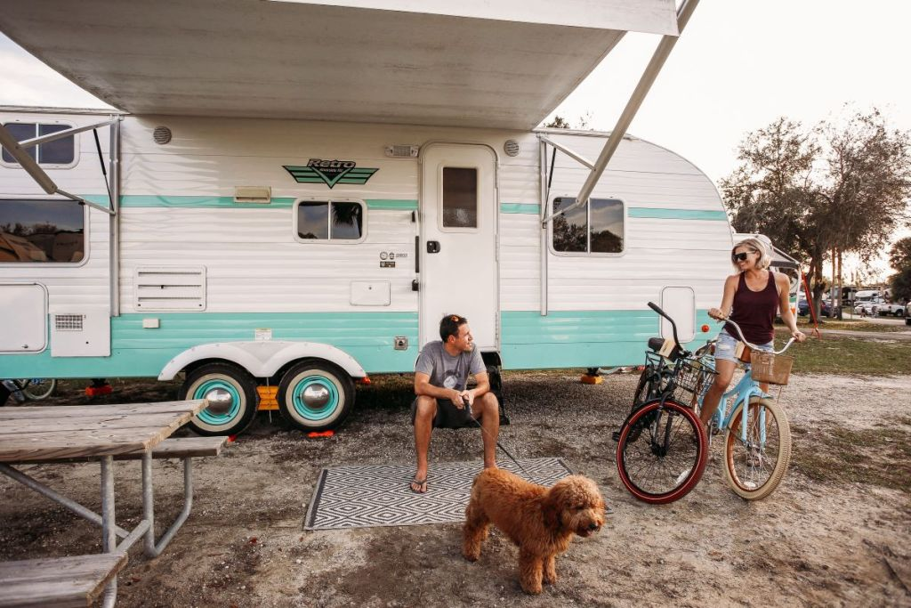 man and woman in front of a camper