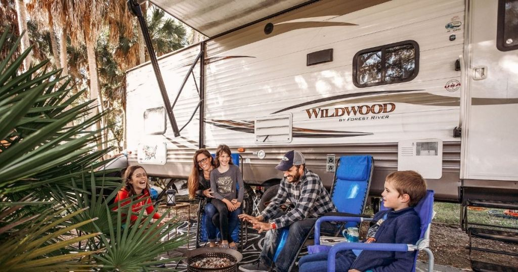 family sitting by a camper