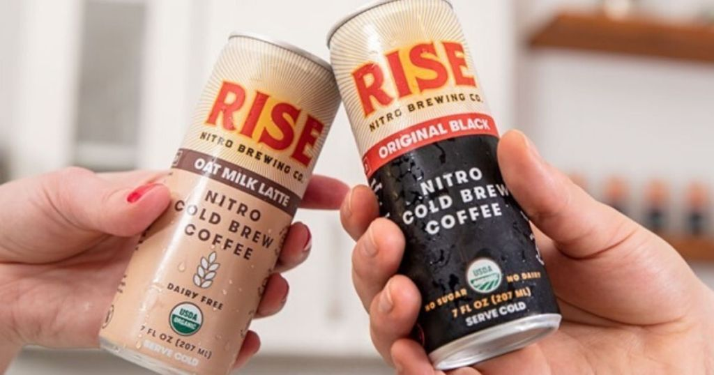 two hand clinking cans of cold brew coffee together